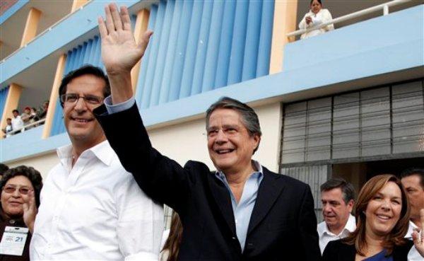 El candidato presidencial opositor Guillermo Lasso, abanderado del partido CREO, centro, saluda a sus seguidores acompañado del aspirante a la vicepresidencia Juan Carlos Solines, izquierda, en las afueras del recinto electoral después de votar en Quito, Ecuador, el domingo 17 de febrero de 2013. (AP Photo/Dominique Riofrio)