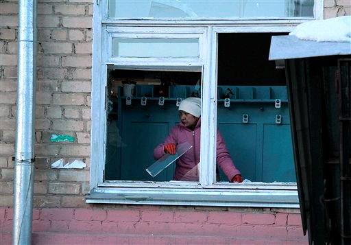 En esta fotografía proporcionada por Chelyabinsk.ru, una mujer retira restos de cristal de una ventana después de la explosión de un meteoro en la región de Cheliábinsk, el viernes 15 de febrero de  2013. (Foto AP/Yevgenia Yemelyanova, Chelyabinsk.ru)