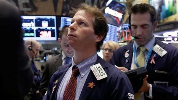 Varios operadores observan movimientos en los indicadores para tomar decisiones en la Bolsa de Valores de Nueva York. El mercado neoyorquino terminó con pérdidas el lunes 11 de febrero de 2013. La imagen corresponde al viernes 8 en Wall Street. (Foto AP/Richard Drew)