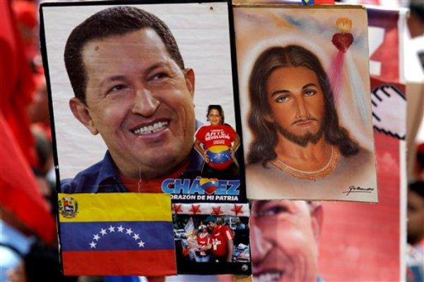 Un retrato del presidente venezolano Hugo Chávez junto con uno de Jesucristo son sostenidos por un partidario de Chávez en una marcha en Caracas el miércoles 23 de enero del 2013.Enormes retratos de Chávez se ven por doquier en Venezuela: en las calles,  carteles, murales, hasta en camisetas. Más de cinco semanas después de que el presidente venezolano se fue a Cuba para someterse a un tratamiento contra el cáncer, el gobierno y sus aliados han alzado honores al mandatario en un fenómeno que raya en el culto a la personalidad.  (Foto AP/Fernando Llano)