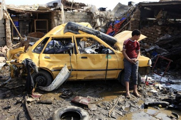 Un chico iraquí permanece cerca de un vehículo destruido en el lugar donde estalló un coche bomba en el distrito de Kazimyah, en el norte de Bagdad, el viernes 8 de febrero de 2013. (AP Foto/ Karim Kadim)