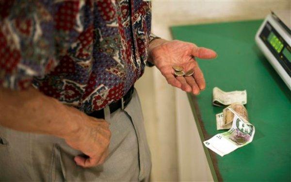 Un hombre busca monedas para pagar su compra en Buenos Aires, Argentina, lunes 4 de febrero de 2013. El gobierno anunció un acuerdo con las grandes cadenas de supermercados para congelar los precios de todos sus productos hasta el 1 de abril, en un intento por contener la inflación. (AP Foto/Víctor R. Caivano)