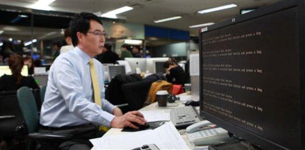 Un empleado trabaja cerca de una pantalla de computadora con mensaje de error en la sala de redacción del canal de noticias por cable YTN al paralizarse el sistema de cómputo de la empresa, el miércoles 20 de marzo de 2013, en Seúl, Corea del Sur. (Foto AP/Yonhap)