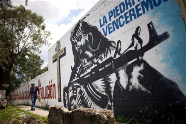 Una persona camina frente a un mural con la imagen de Jesucristo sosteniendo un fusil pintado por el colectivo La Piedrita, en el barrio 23 de Enero, en Caracas, Venezuela, el 16 de septiembre de 2010. Tras el fallecimiento del presidente venezolano Hugo Chávez, el 5 de marzo de 2013, cientos de organizaciones llamadas ?colectivos? están en alerta y en pie de guerra para defender la causa chavista. (Foto AP/Ariana Cubillos, Archivo)