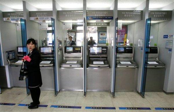 Una cliente frente a una fila de cajeros automáticos en una sucursal del banco Shinhan después que se paralizaron las redes informáticas del banco el miércoles 20 de marzo de 2013, en Seúl, Corea del Sur. (Foto AP/Ahn Young-joon)