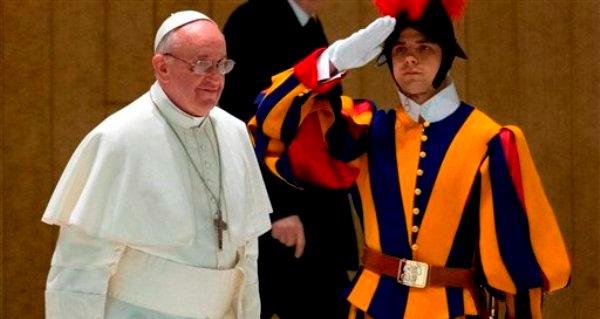 El papa Francisco pasa junto a un guardia suizo a su llegada a una reunión con los medios de comunicación en la sala Pablo VI, en el Vaticano, el sábado 16 de marzo de 2013. (Foto AP/Michael Sohn)