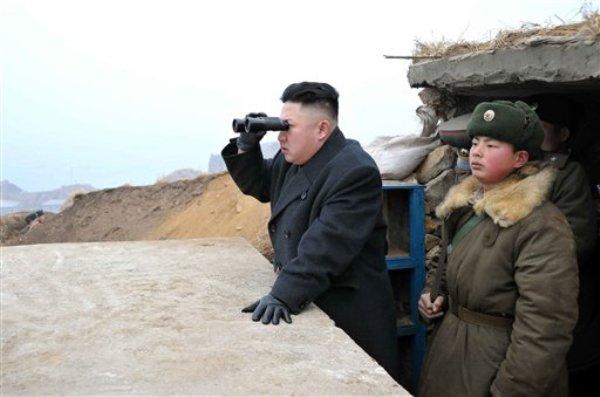 El líder de Corea del Norte, Kim Jong Un, centro, en una foto del 7 de marzo del 2013 difundida por la Agencia Central de Corea del Norte (KCNA) usa binoculares desde un puesto de observación de la unidad militar del islote Jangjae, situado en el extremo sur del suroeste de Corea del Norte, frontera con Corea del Sur.