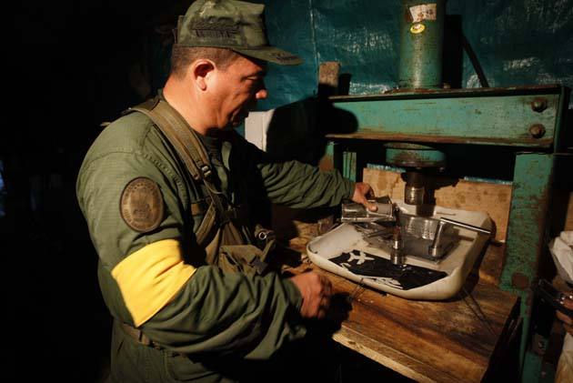 A Venezuelan national guard inspects the site of a cocaine laboratory, located along the border with Colombia, in the state of Zulia