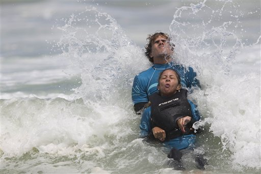Ayudada por un voluntario de AdaptSurf, Monique Oliveira cabalga una ola en la playa de Barra de Tijuca, en Río de Janeiro, el 16 de marzo del 2013. AdaptSurf ayuda a personas con incapacidades a hacer surf en las playas de Río. (AP Photo/Felipe Dana)