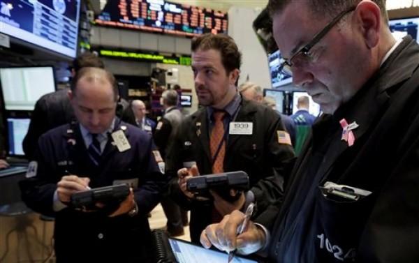 Varios corredores trabajan en el piso de la Bolsa de Valores de Nueva York, el martes 19 de marzo de 2013. Los mercados europeos se estabilizaron el martes 26 de marzo del mismo año, un día después de sufrir una fuerte agitación por una declaración de un alto funcionario europeo de que el rescate financiero a Chipre era un modelo para el futuro. (Foto AP/Richard Drew)