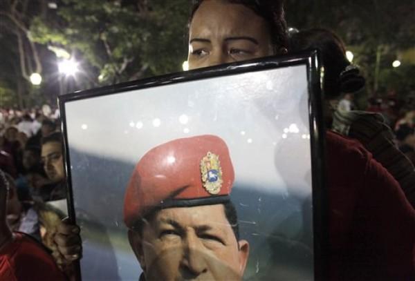 Una seguidora del presidente venezolano Hugo Chávez llora mientras sostiene un afiche con su fotografía durante un mitin. (Foto de Archivo AP/Ariana Cubillos)