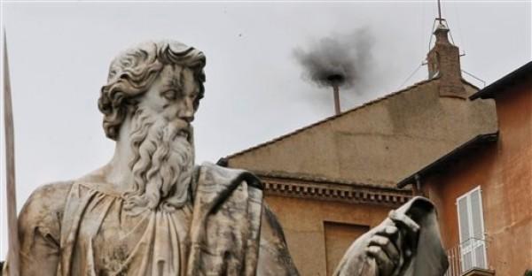 Humo negro sale de la chimenea de la Capilla Sixtina luego de que los cardenales votaron en el segundo día del cónclave para elegir un nuevo papa en la plaza de San Pedro, en el Vaticano, el miércoles 13 de marzo de 2013. En primer plano está la estatua de San Pablo. (Foto AP/Dmitry Lovetsky)