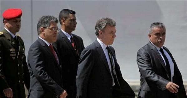 El presidente de Colombia Juan Manuel Santos (centro) a su llegada a la ceremonia fúnebre de Hugo Chávez el 8 de marzo del 2013 en Caracas. Lo acompaña el canciller venezolano Elías Jaua (segundo desde la izquierda). (AP Photo/Rodrigo Abd)