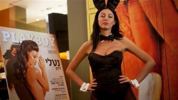 Una modelo vestida como conejita de Playboy posa con la portada de la primera edición en hebreo de esta revista para caballeros en Tel Aviv, Israel, el martes 5 de marzo de 2013. (AP Foto/Ariel Schalit)