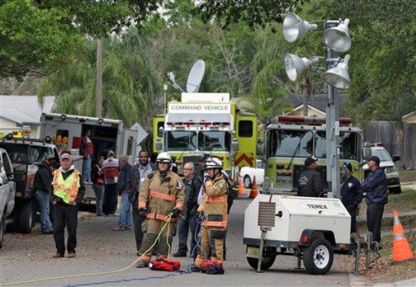 Los bomberos del condado de Hillsborough, Florida, trabajan el sábado 2 de marzo del 2013 cerca de donde se abrió un hoyo en la tierra el jueves por la noche y se tragó a un hombre que estaba en su dormitorio. (AP Foto/Chris O'Meara)