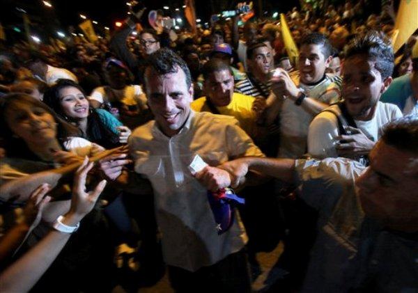 El candidato opositor venezolano Henrique Capriles, en el centro, es rodeado por simpatizantes durante una marcha contra la violencia en Caracas, Venezuela, el lunes 1 de abril de 2013. (AP foto/Fernando Llano)