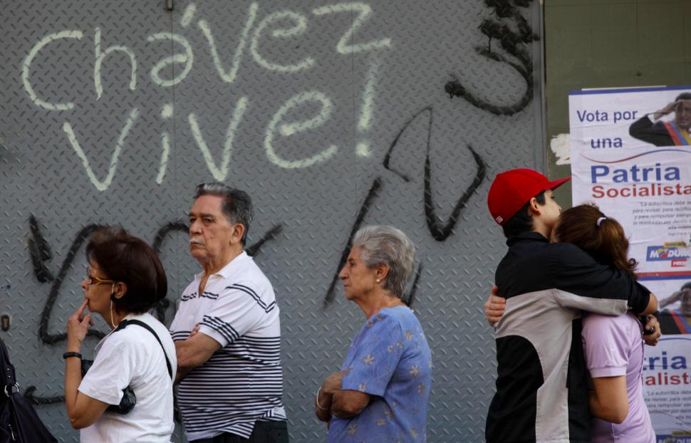 """Residentes hacen fila para votar en las elecciones presidenciales venezolanas en Caracas, delante de un letrero que dice """"Chávez vive"""", la mañana del domingo 14 de abril de 2013. El presidente encargado Nicolás Maduro, heredero del fallecido mandatario Hugo Chávez, se enfrenta al candidato opositor Henrique Capriles. (AP foto/Enric Martí)"""