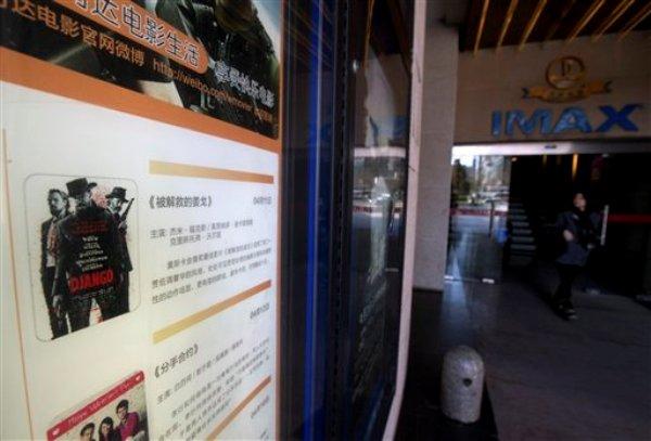 """Una mujer sale de un cine Wanda donde se anuncia la película ?Django Unchained"""" en Beijing, China, el jueves 11 de abril de 2013. ?Django Unchained"""" fue retirada de los cines horas después de su estreno. Sus distribuidores argumentaron problemas técnicos, pero algunos sospechan que se trata de censura. (Foto AP/Andy Wong)"""