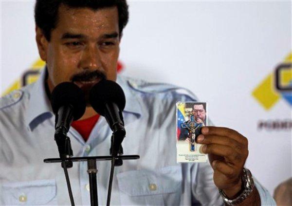 El presidente encargado de Venezuela y candidato oficialista Nicolás Maduro muestra una foto del difunto Hugo Chávez y un crucifijo mientras habla con la prensa luego de sufragar en las elecciones presidenciales en Caracas, Venezuela, el domingo 14 de abril de 2013.  Maduro, heredero de Chávez, se enfrenta al candidato opositor Henrique Capriles. (AP foto/Ariana Cubillos)