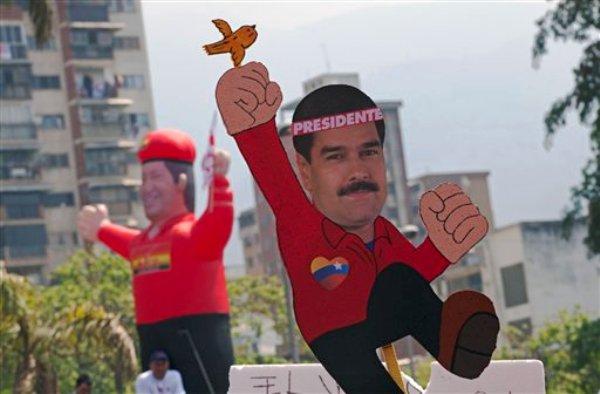 Un dibujo del presidente encargado y candidato oficialista Nicolás Maduro con un pájaro en su mano y una figura inflable del fallecido mandatario Hugo Chávez son llevados por simpatizantes de Maduro a su acto de cierre de campaña en Caracas, Venezuela, el jueves 11 de abril de 2013.(AP foto/Ramon Espinosa)
