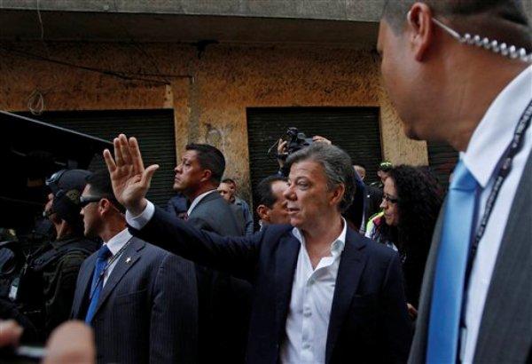 El presidente colombiano Juan Manuel Santos saluda a los residentes durante su primera visita al área conocida como ?calle del Bronx?, el principal expendio de drogas de Colombia, en Bogotá, el lunes 1 de abril de 2013. (Foto AP/Fernando Vergara)