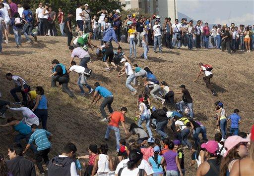 Simpatizantes de la oposición y estudiantes escapan del gas lacrimógeno después de chocar con la policía antidisturbios cuando intentaban bloquear una autopista en el barrio de Altamira, Caracas, Venezuela, el lunes 15 de abril del 2013. Las tropas de la Guardia Nacional dispersaron a los que protestaban por los resultados de la elección presidencial especial del domingo, cuyos estrechos resultados a favor del oficialista Nicolás Maduro fueron rechazados por el candidato opositor Henrique Capriles, quien demandó un conteo de todos los votos. (AP Foto/Ramon Espinosa)