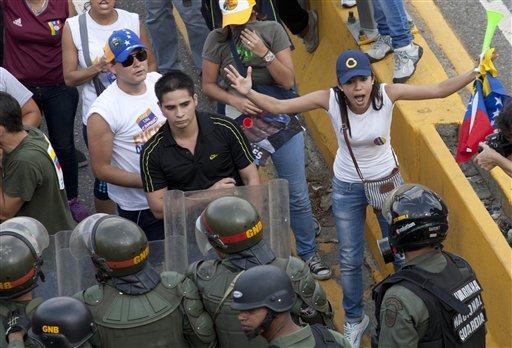 Simpatizantes de la oposición y estudiantes confrontan a policías antidisturbios mientras bloquean una autopista en el barrio de Altamira, Caracas, Venezuela, el lunes 15 de abril del 2013. Las tropas de la Guardia Nacional dispersaron a los que protestaban por los resultados de la elección presidencial especial del domingo, cuyos estrechos resultados a favor del oficialista Nicolás Maduro fueron rechazados por el candidato opositor Henrique Capriles, quien demandó un conteo de todos los votos. (AP Foto/Ramon Espinosa)