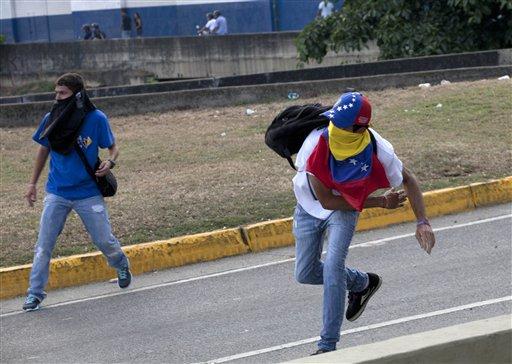 Manifestantes lanzan piedras contra la policía antidisturbios en medio de enfrentamientos entre opositores y estudiantes con las autoridades que dispersaron una protesta que bloqueaba una autopista en el barrio de Altamira, Caracas, Venezuela, el lunes 15 de abril del 2013. Las tropas de la Guardia Nacional dispersaron a quienes protestaban por los resultados de la elección presidencial especial del domingo, cuyos estrechos resultados a favor del oficialista Nicolás Maduro fueron rechazados por el candidato opositor Henrique Capriles, quien demandó un conteo de todos los votos. (AP Foto/Ramon Espinosa)