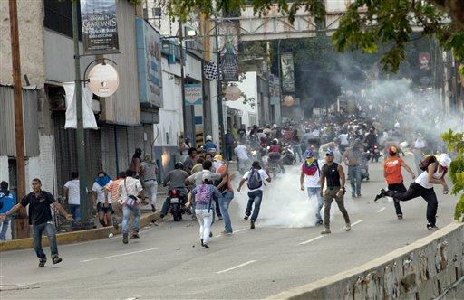 Simpatizantes de la oposición y estudiantes chocan contra soldados de la Guardia Nacional y policías antidisturbios que lanzan gases lacrimógenos contra una protesta en una autopista del barrio de Altamira, Caracas, Venezuela, el lunes 15 de abril del 2013. Las tropas de la Guardia Nacional dispersaron a los que protestaban por los resultados de la elección presidencial especial del domingo, cuyos estrechos resultados a favor del oficialista Nicolás Maduro fueron rechazados por el candidato opositor Henrique Capriles, quien demandó un conteo de todos los votos. (AP Foto/Ramon Espinosa)