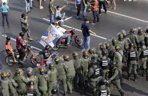 Soldados y vehículos de la Guardia Nacional permanecen en una calle cerca del centro de Caracas, Venezuela, el lunes 15 de abril del 2013. El consejo electoral proclamó al candidato oficialista y presidente encargado, Nicolás Maduro, como ganador de la elección presidencial especial del domingo mientras su rival, el opositor Henrique Capriles, rechazó los resultados. (AP foto/Fernando Llano)