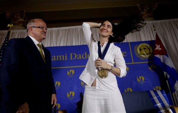 La bloguera y activista cubana Yoani Sánchez, derecha, se ajusta el cabello tras recibir una medalla de manos de Eduardo Padrón, izquierda, presidente del Miami Dade College, después de hablar en la Freedom Tower de esa universidad, el lunes 1 de abril de 2013, en Miami. (Foto AP/Lynne Sladky)