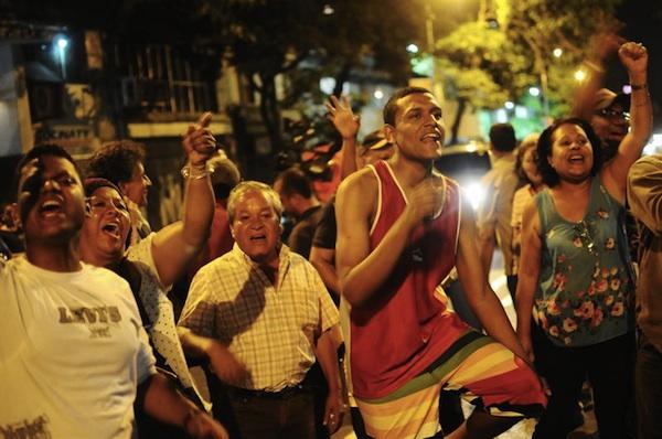 Foto: seguidores del Gobierno venezolano y opositores gritan consignas en las puertas de un centro de votación hoy, domingo 14 de abril de 2013, en Caracas (Venezuela), luego de que el Consejo Nacional Electoral (CNE) oficializó el cierre de los colegios utilizados en los comicios presidenciales que tuvieron lugar en Venezuela para elegir al presidente que sucederá a Hugo Chávez. EFE/William Viera