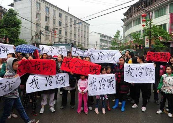 """Habitantes de Lingguan en Baoxing salieron a las calles con carteles que decían """"Tenemos hambre y frío""""."""
