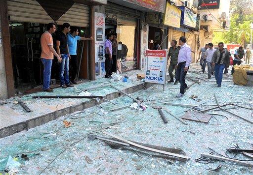 Agentes de la policía conversan con los propietarios de establecimientos comerciales cerca de donde estalló una poderosa bomba en el distrito de Marjeh, en el centro de Damasco, Siria, el martes 30 de abril de 2013. Al menos 13 personas murieron y 70 resultaron heridas en el atentado, según las autoridades. (AP Foto/SANA)