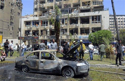 Personal de seguridad inspecciona un automóvil incendiado en el lugar donde estalló una poderosa bomba en el distrito de Marjeh, en el centro de Damasco, Siria, el martes 30 de abril de 2013. Al menos 13 personas murieron y 70 resultaron heridas en el atentado, según las autoridades. (AP Foto/SANA)