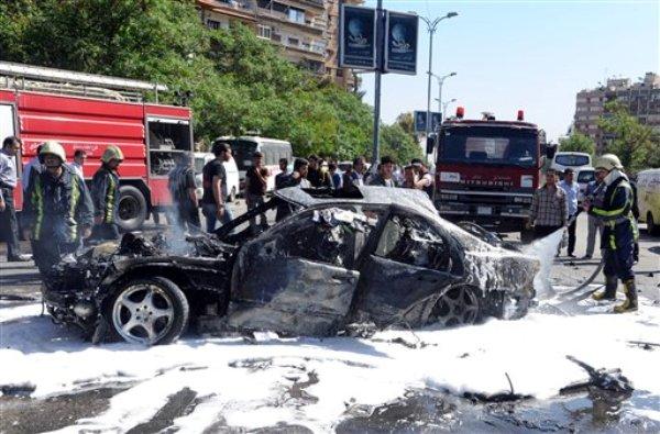 Fotografía difundida por la agencia noticiosa oficial siria SANA, en la que aparecen bomberos extinguiendo las llamas de un vehículo dañado tras el estallido de una bomba en el barrio de Mazzeh, en Damasco, el lunes 29 de abril de 2013. (Foto AP/SANA)