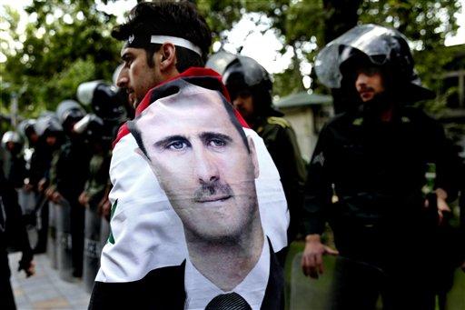 Un hombre envuelto con una bandera siria que lleva el retrato del presidente Bashar Assad camina entre policías antidisturbios durante una manifestacion antisraelí frenete a la oficina de la ONU en Teherán,Irán, el lunes 6 de mayo de 2013. Irán condenó losrecientes ataques aéreos israelies contra Siria. (AP Foto/Ebrahim Noroozi)