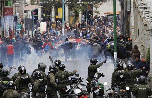 Manifestantes huyen ante los efectos de las bombas lacrimógenas lanzadas por la policía durante una marcha de mineros que protestan en La Paz, Bolivia, el jueves 16 de mayo de 2013. (AP Photo/Juan Karita)