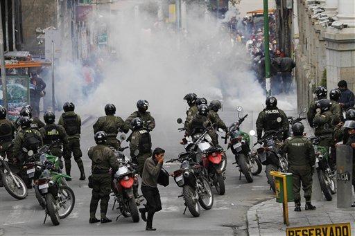 Policías se protegen de sus prpios gases lacrimógenos lanzados para dispersar una marcha de mineros en una protesta callejera en La Paz, Bolivia, el jueves 16 de mayo 2013. (AP Photo/Juan Karita)