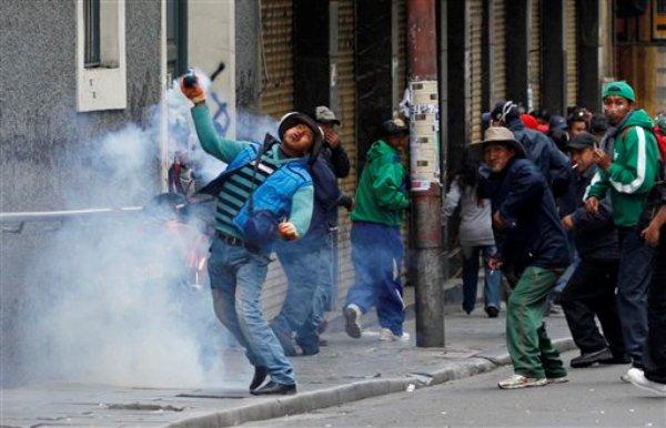 Un manifestante devuelve un casquillo de bomba de gas lacrimógeno  la policía en una protesta callejera en La Paz, Bolivia, el jueves 16 de mayo 2013. (AP Photo/Juan Karita)