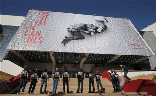 """Un anuncio del Festival de Cine de Cannes en el frente del Palacio del Festival de Cannes el lunes 13 de mayo de 2013. El anuncio muestra a Paul Newman y Joanne Woodward besándose en el plató de """"A New Kind of Love"""", dirigida por Melville Shavelson en 1963. El Festival de Cine de Cannes arranca el 15 de mayo. (Foto AP Photo/Lionel Cironneau)"""