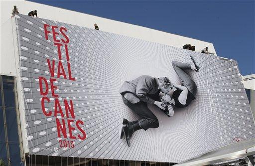 """Trabajadores colocan un anuncio del Festival de Cine de Cannes en el frente del Palacio del Festival de Cannes el lunes 13 de mayo de 2013. El anuncio muestra a Paul Newman y Joanne Woodward besándose en el plató de """"A New Kind of Love"""", dirigida por Melville Shavelson en 1963. El Festival de Cine de Cannes arranca el 15 de mayo. (Foto AP Photo/Lionel Cironneau)"""
