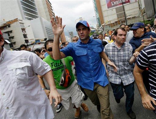 El dirigente opositor Henrique Capriles saluda a sus partidarios durante una marcha del Primero de Mayo en Caracas. Las autoridades electorales iniciaron el lunes el proceso de auditoría complementaria de las elecciones del 14 de abril sin la presencia de la oposición, que rechazó participar en la revisión alegando que no fueron incluidos todos los elementos del proceso. (AP Foto/Fernando Llano)