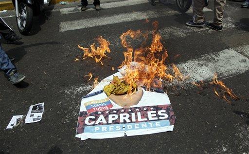 """Simpatizantes del gobierno """"chavista"""" quema un poster electoral del candidato presidencial de oposición Henrique Capriles en Los Teques, en las afueras de Caracas, Venezuela, el jueves 16 de abril 2013. El presidente electo Nicolás Maduro culpa a Capriles por las siete muertas que el gobierno dice que se registraron en disturbios post electorales. El gobierno proporcionó los nombres de algunas personas que dice que fueron víctimas de opositores pero ninguna evidencia concreta. Capriles exige un recuento de votos de la disputada elección del domingo ganada por Maduro. (AP Foto/Ariana Cubillos)"""