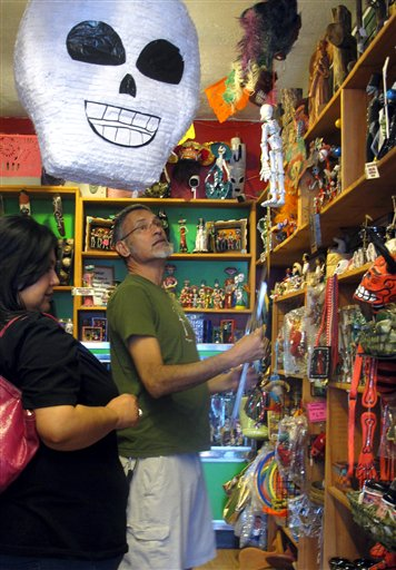 En esta foto del 8 de mayo del 2013 se ven los artículos ofrecidos por un comercio de Albuquerque sobre el 'Día de los Muertos'. Disney anunció el día 7 que retiraba una solicitud de pantentar la marca 'Día de los Muertos' después de una reacción contraria de activistas hispanos que cobró fuerza en las redes sociales (AP Foto/Russell Contreras)
