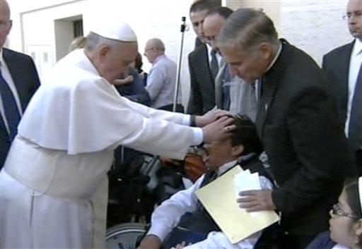 En esta imagen tomada de un video proporcionado por APTN, el papa Francisco coloca sus manos sobre la cabeza de un hombre joven el domingo 19 de mayo de 2013, tras celebrar misa en la Plaza de San Pedro. (Foto AP/APTN)