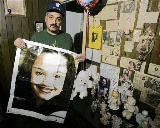 Felix DeJesus sostiene un afiche con la imagen de su hija desaparecida en una foto de archivo del 3 de marzo del 2004 frente a un altar de homenaje en la sala de su casa en Cleveland. La policía de Cleveland dijo que halló a dos mujeres que desaparecieron cuando eran adolescentes hac una década fueron halladas vivas en un área residencial a más de 3 kilómetros (2 millas) del centro de la ciudad. Grupos de personas jubilosas se congregaron en la calle cerca de la casa donde la policía encontró el lunes 6 de mayo del 2013, a Amanda Berry, Gina DeJesus y a una tercera mujer no identificada. (Foto AP/Tony Dejak)