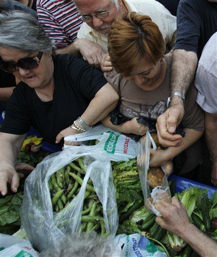 La gente se empuja para conseguir verduras mientras vendedores reparten comida gratis durante una protesta en Atenas el miércoles 15 de mayo de 2013. (Foto de AP/Thanassis Stavrakis)
