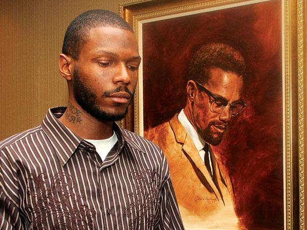 Malcolm Shabazz junto a un cuadro de su abuelo el activista Malcolm X