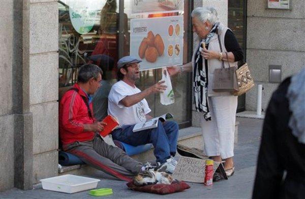 Jesús (izquierda), de 49 años, y Paco (centro), de 50, ambos de España, reciben comida de una mujer mientras piden ayuda en las calles de Madrid el lunes 27 de mayo de 2013. España ha estado en recesión por casi cuatro años y tiene una tasa de desempleo de 27,2%. (Foto AP/Andres Kudacki)